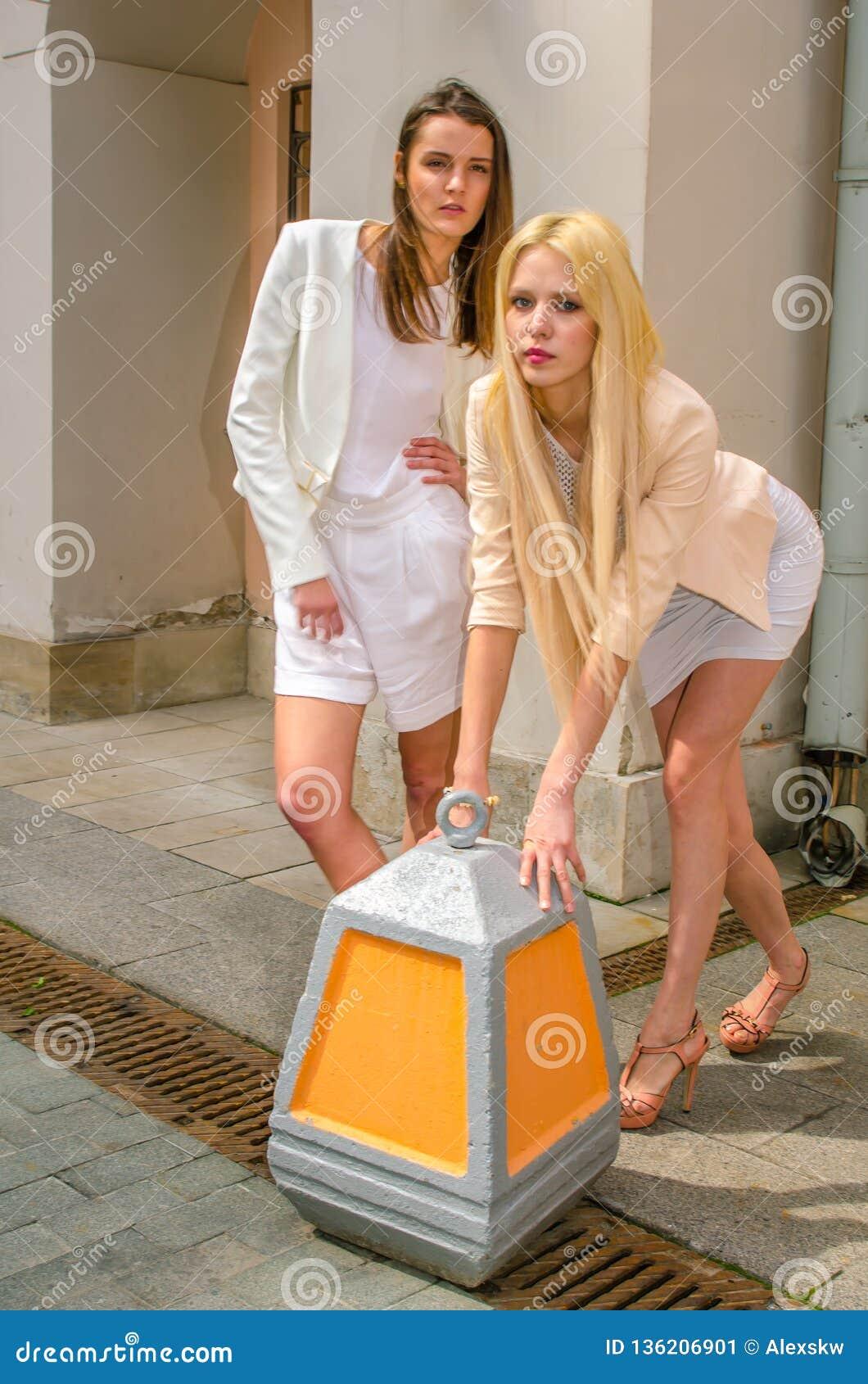 2 друз блондинка и брюнет в белых платьях представляя на улице старого города