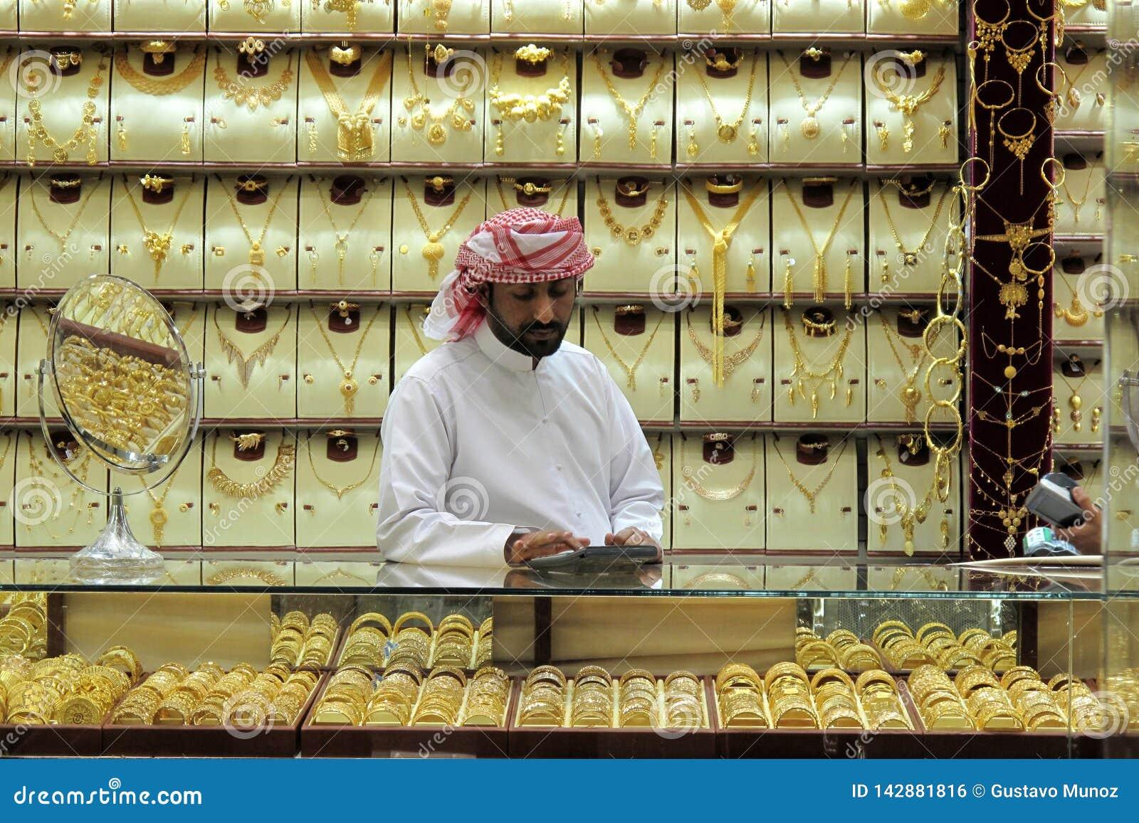 Дубай, ОАЭ - 3-ье марта 2017: Продавец золота внутри ювелирных изделий в souk золота Дубай