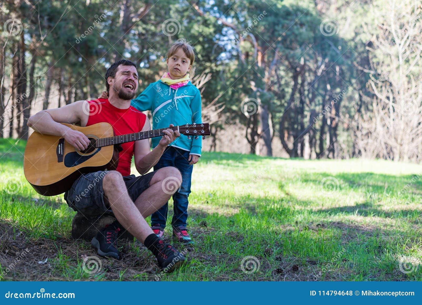 Дуэт семьи: Папа играя гитару с его дочерью, открытый космос для вашего текста