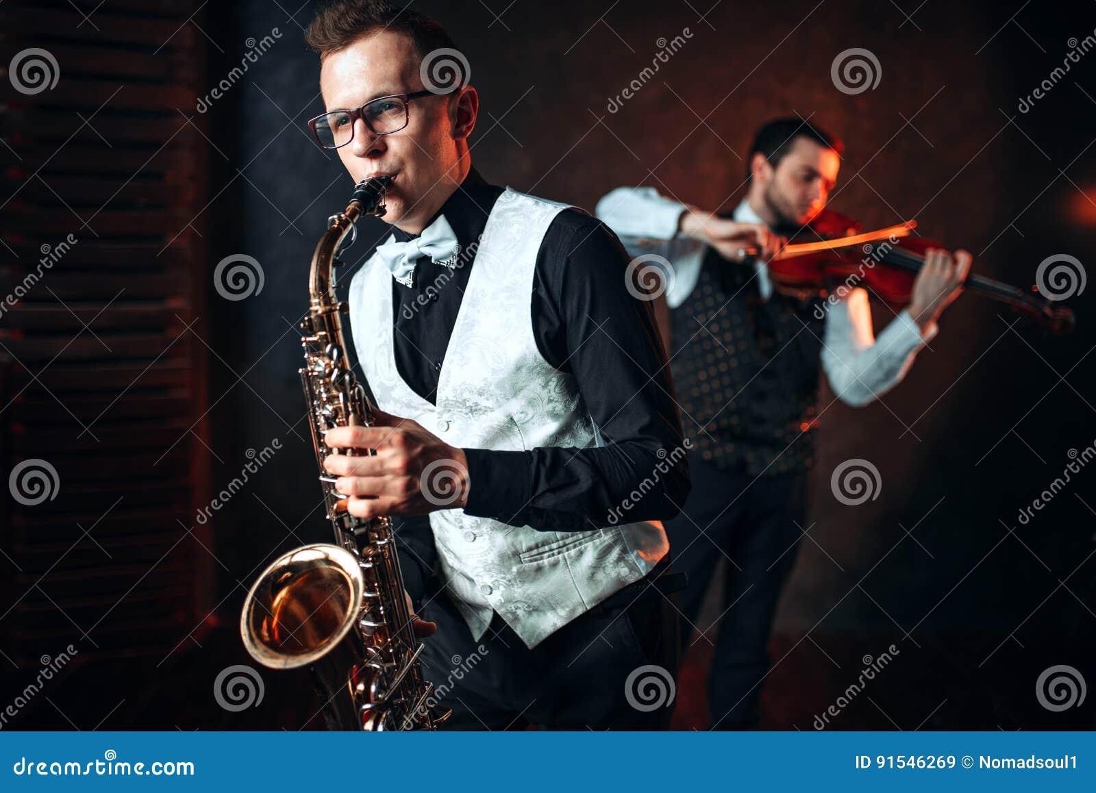 Дуэт человека и скрипача саксофона играя классическую мелодию