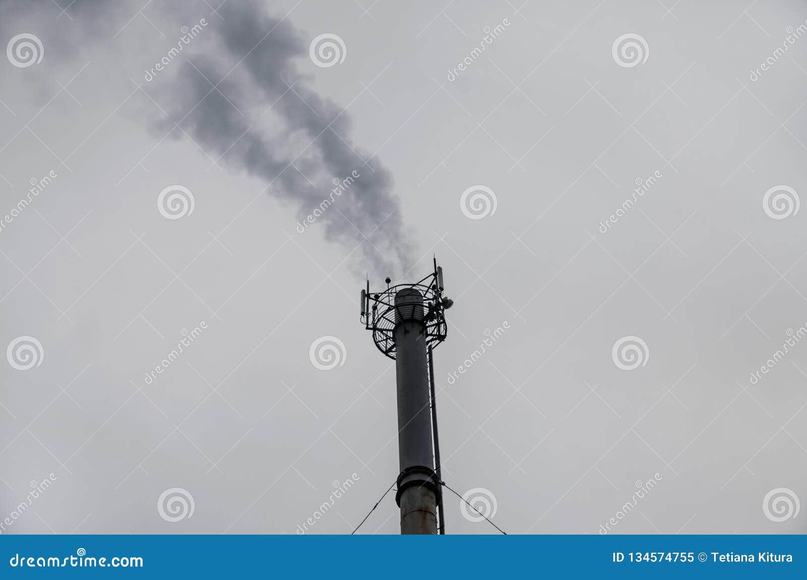 Дым от трубы на предпосылке серого неба