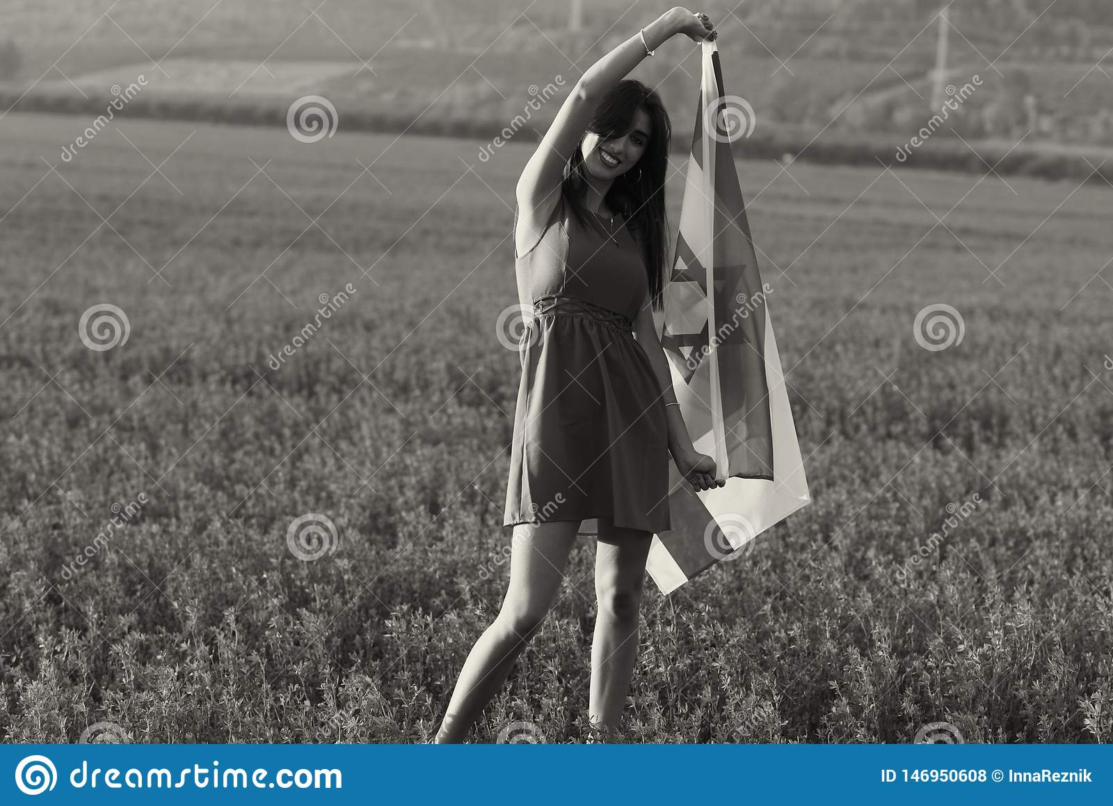 Еврейская девушка с флагом Израиля на изумляя ландшафте красивым летом