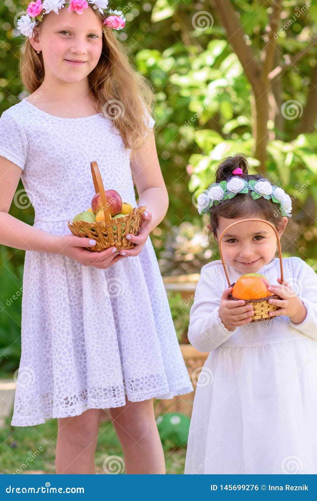 Еврейский праздник Shavuot Маленькие девочки HarvestTwo в белом платье держат корзину со свежими фруктами в саде лета