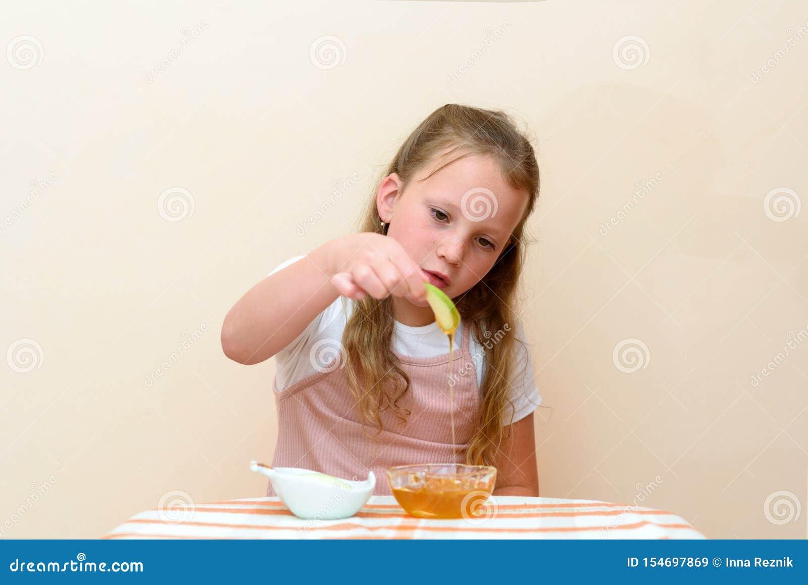 Еврейский ребенок окуная куски яблока в мед на Rosh HaShanah