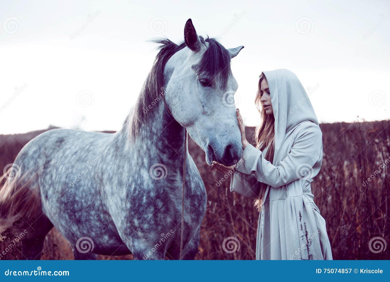 девушка в с капюшоном плаще с лошадью, влиянием тонизировать