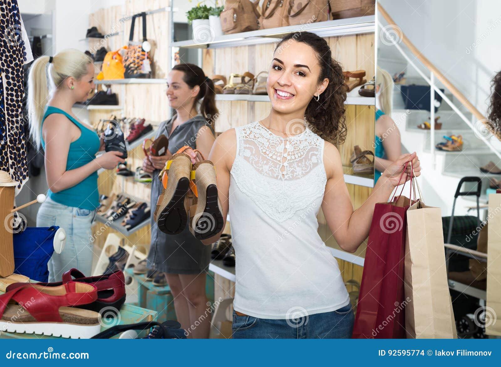3 девушки держащ бумажные хозяйственные сумки в бутике