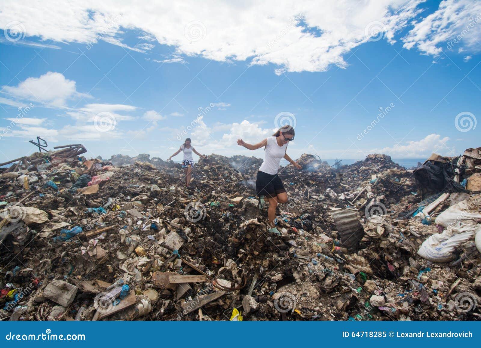 2 девушки идя среди погани на свалке мусора
