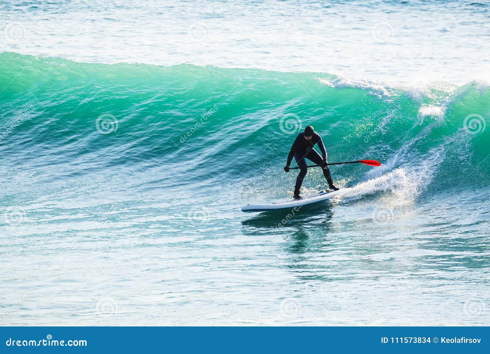 Езда серфера дальше стоит вверх доска затвора на океанских волнах Стойте вверх восхождение на борт затвора в море