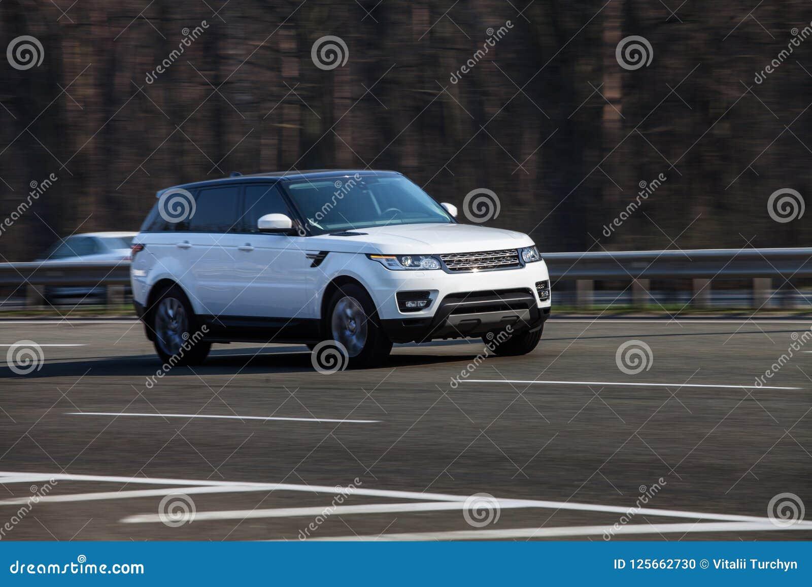 Езды белизны Range Rover на дороге Против предпосылки запачканных деревьев