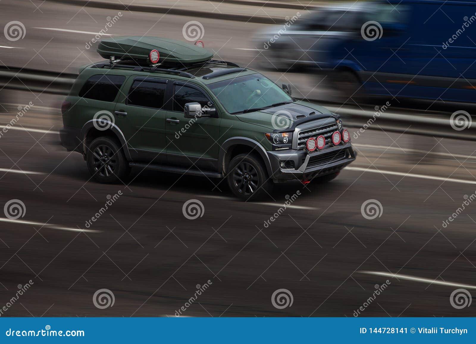 Езды зеленого цвета Тойота на дороге Против предпосылки запачканных деревьев