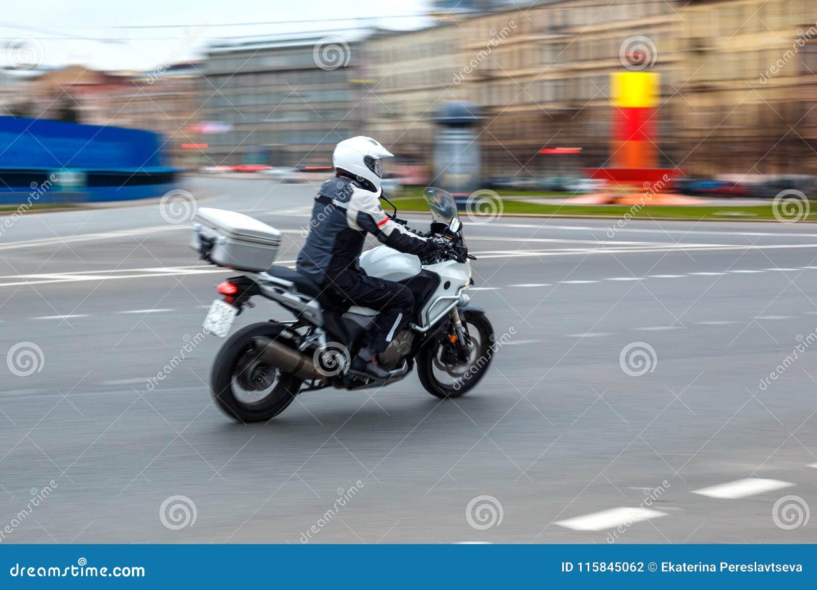 Езды мотоцикла с скоростью на дорогах города