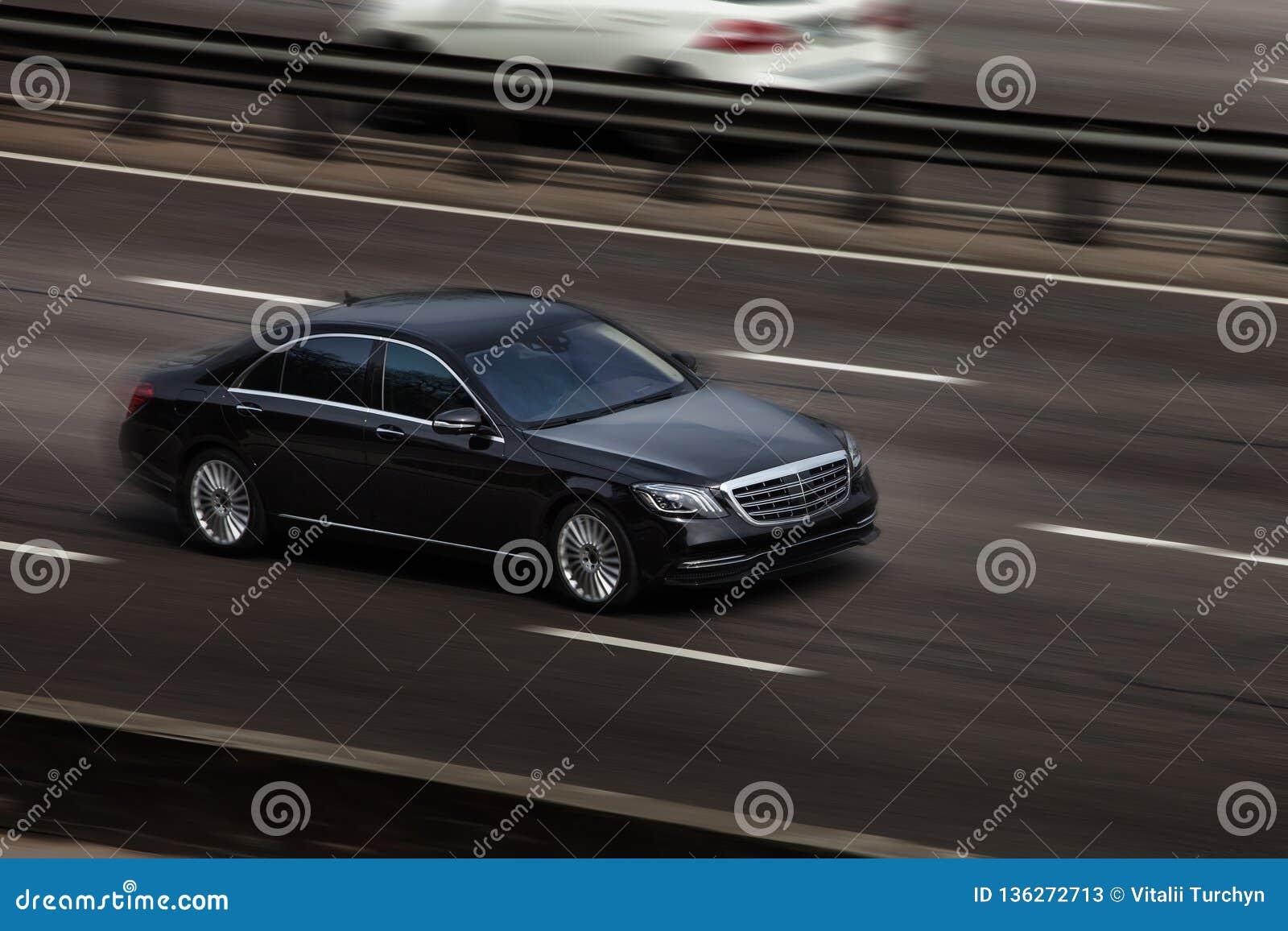 Езды Benz Мерседес черные на дороге Против предпосылки запачканных деревьев
