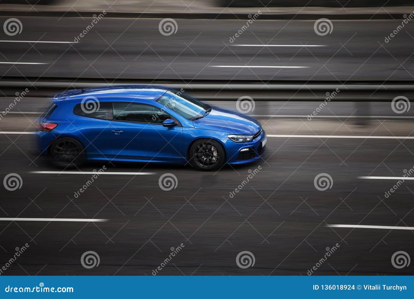 Езды scirocco VW голубые на дороге Против предпосылки запачканных деревьев