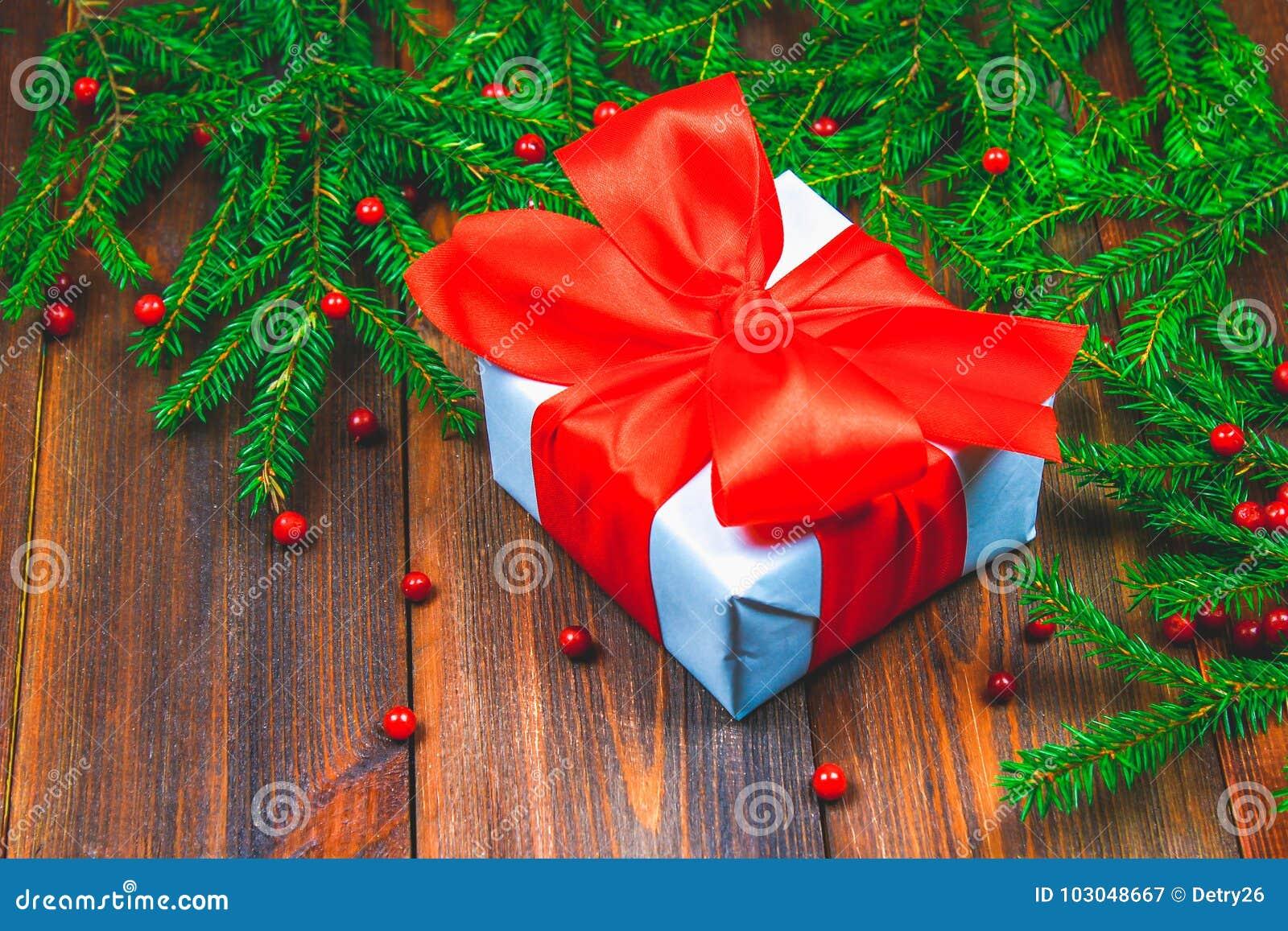 Елевые ветви с красными ягодами на деревянном столе В центре коробки с настоящими моментами перевязанные смычки Рождество, праздн