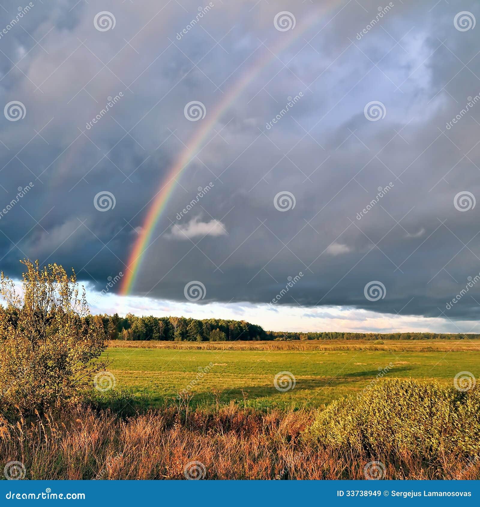Естественная радуга над полем осени и темным небом.
