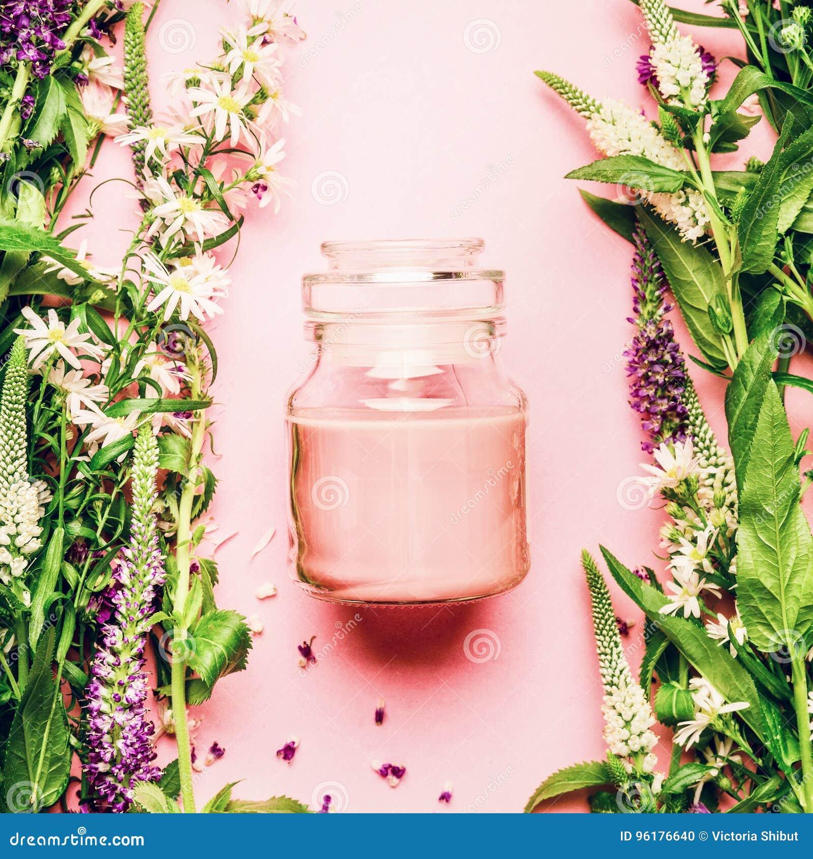 Естественная травяная концепция косметики заботы кожи Стеклянный опарник с cream и свежими травами и цветками на розовой предпосы