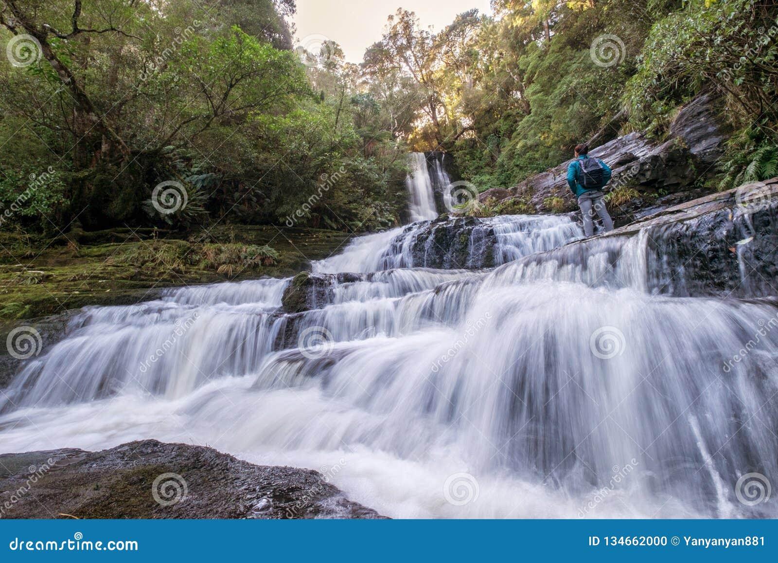 Естественный ландшафт положения hiker перед водопадом, Новой Зеландией