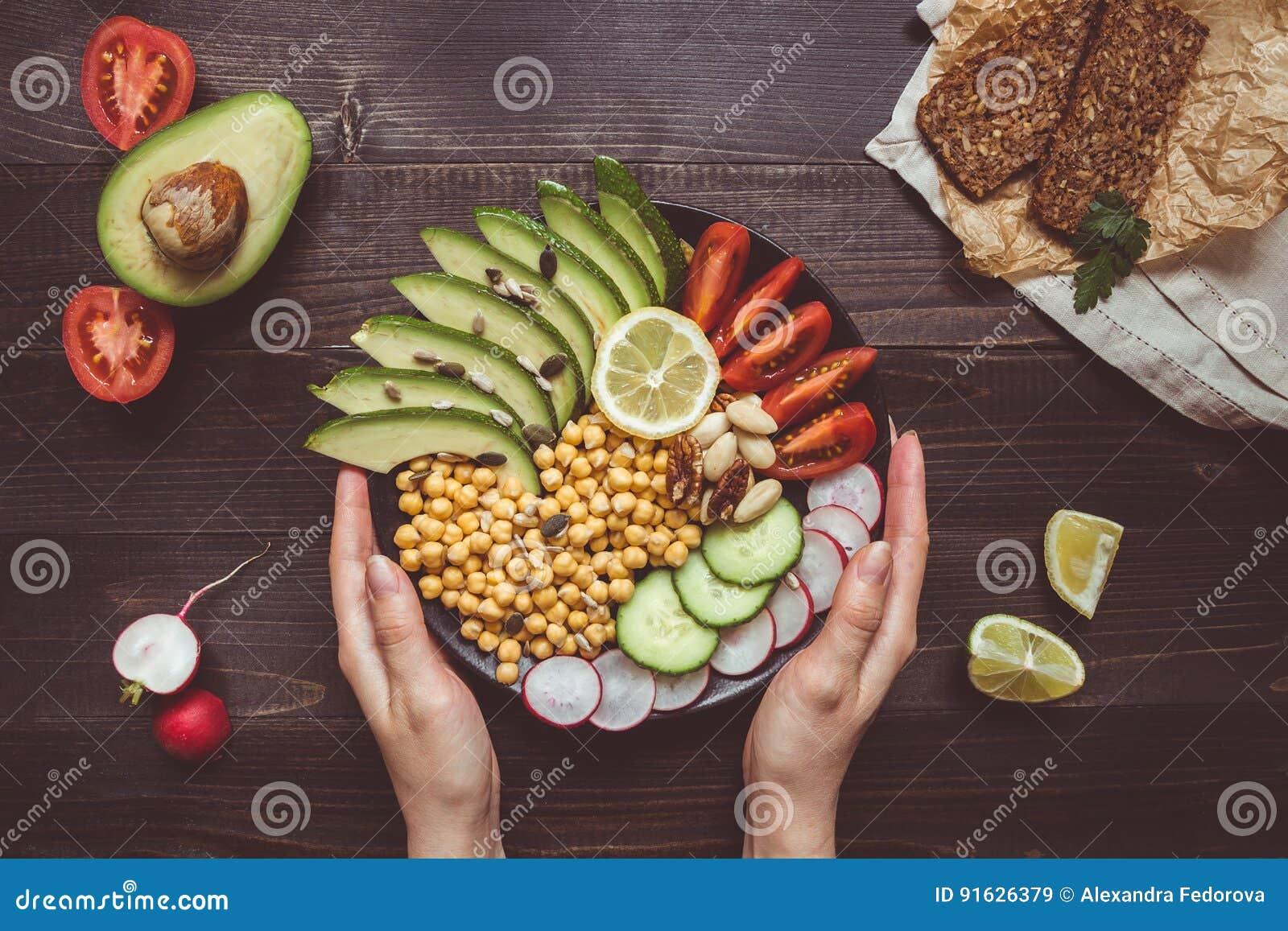 еда принципиальной схемы здоровая Руки держа здоровый салат с нутом и овощами Еда Vegan vegetarian диетпитания