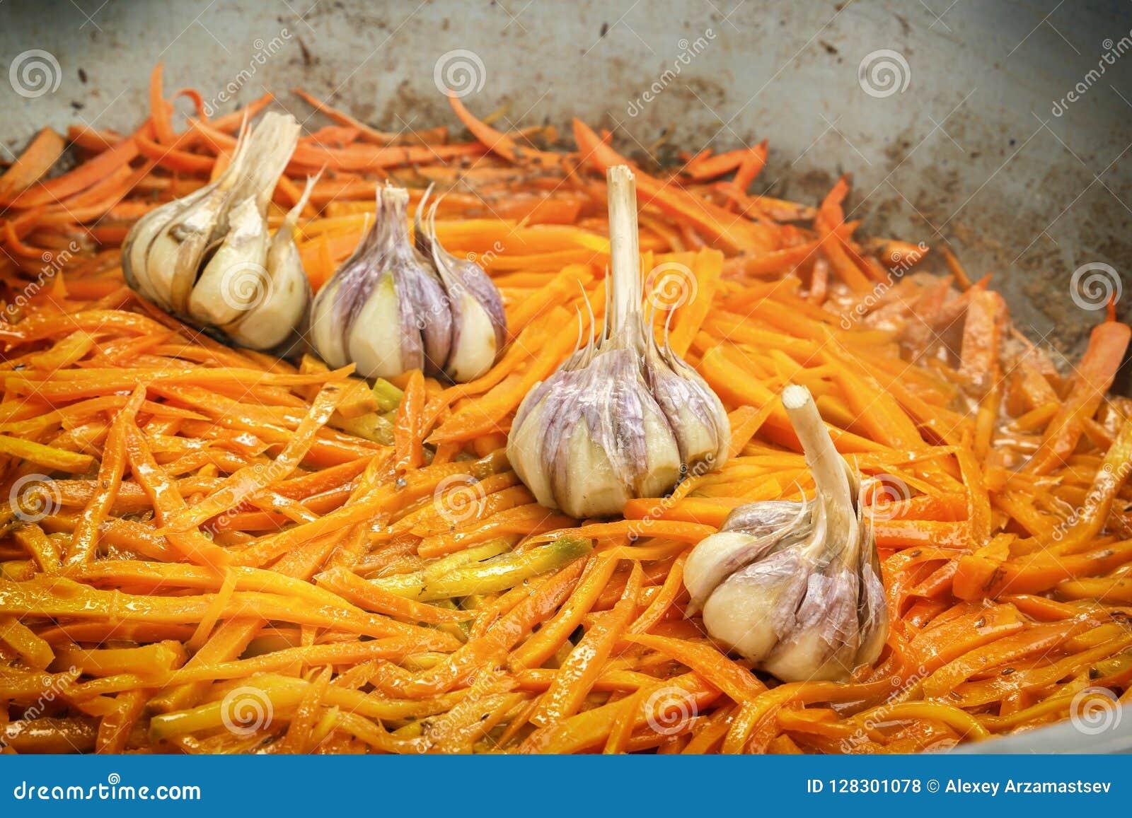 Жарят в духовке в большой сковороде на улице для того чтобы подготовить морковей и чеснок традиционное азиатское блюдо pilaf