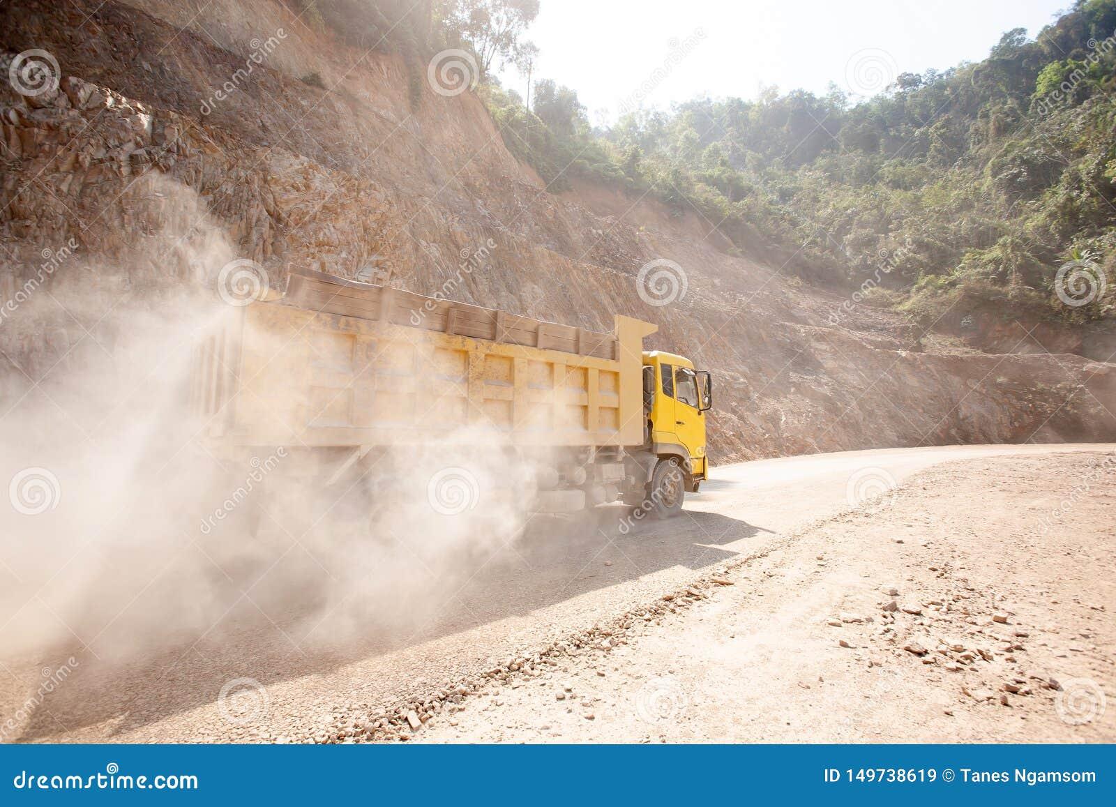 Желтая деятельность самосвала на пылевоздушной дороге на строительной площадке, новом строительстве дорог горы около границы Лаос