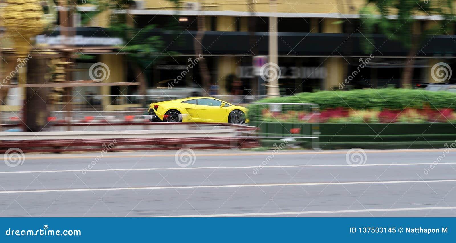 Желтое Lamborghini Gallardo управляя очень быстрым на улице нерезкость предпосылки запачкала движение frisbee задвижки скача к