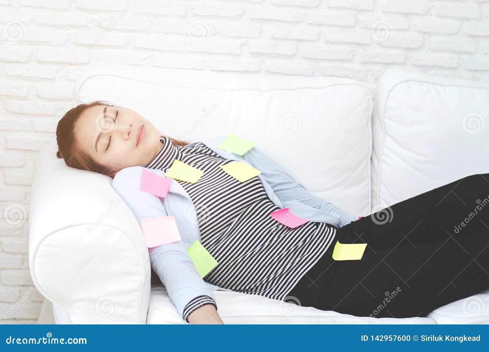 Желтые, зеленые и розовые бумажные листы на женщине которая спит и вымотанный от работы
