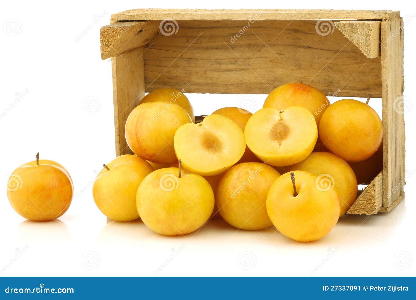 Желтые сливы и отрезок одно в деревянной клети