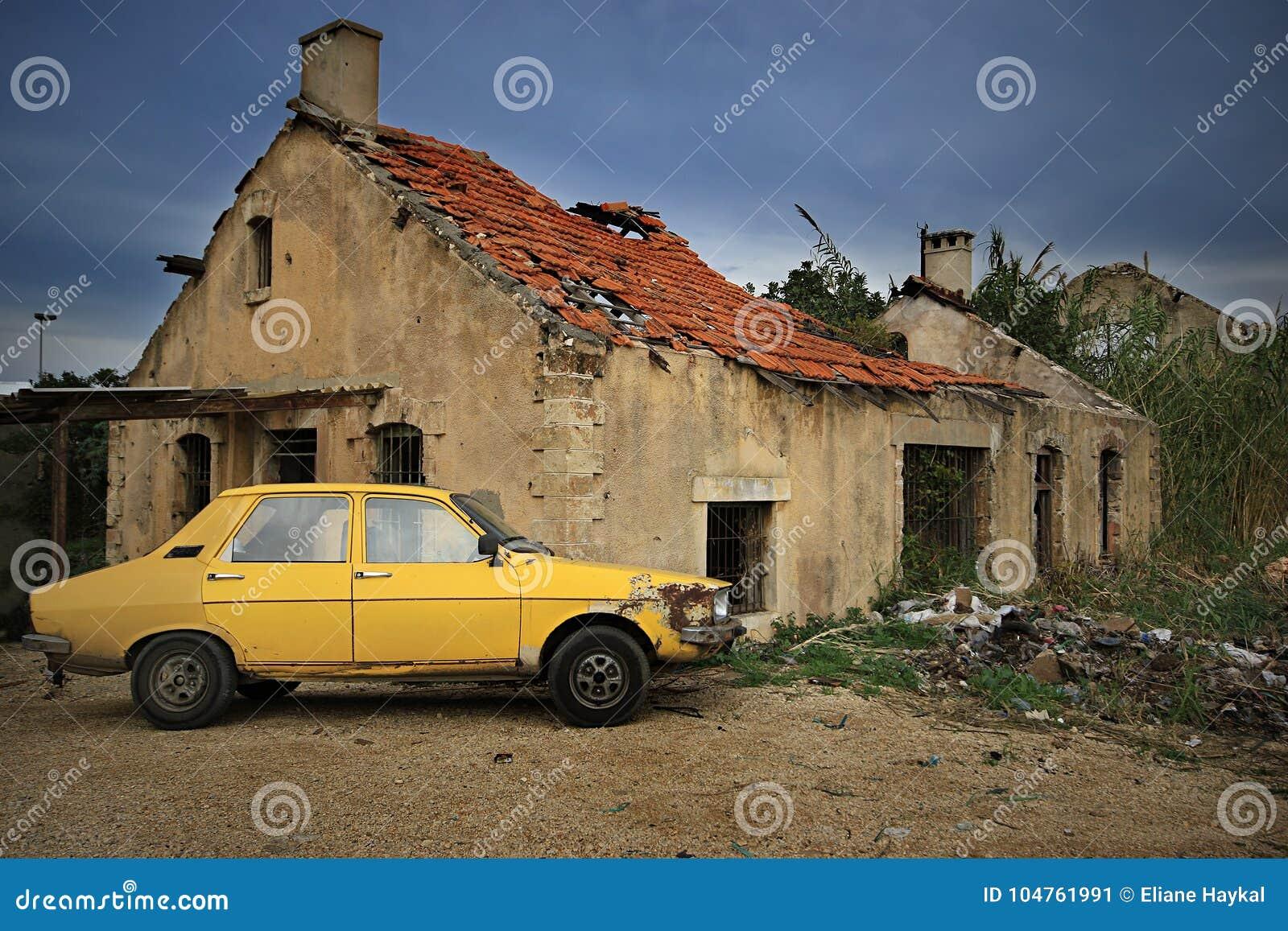 Желтый автомобиль и разрушанный дом