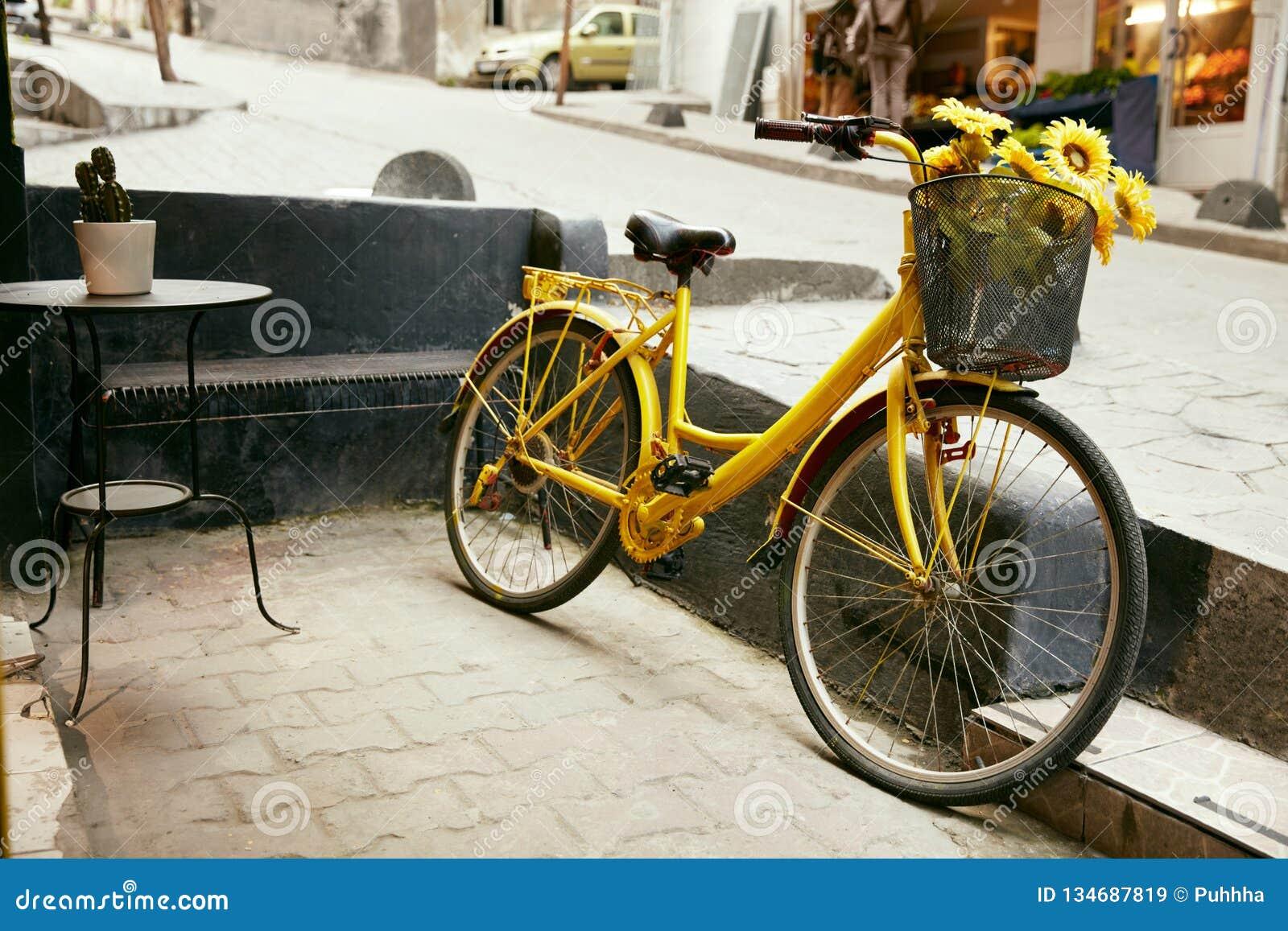 Желтый велосипед с корзиной солнцецветов на улице города