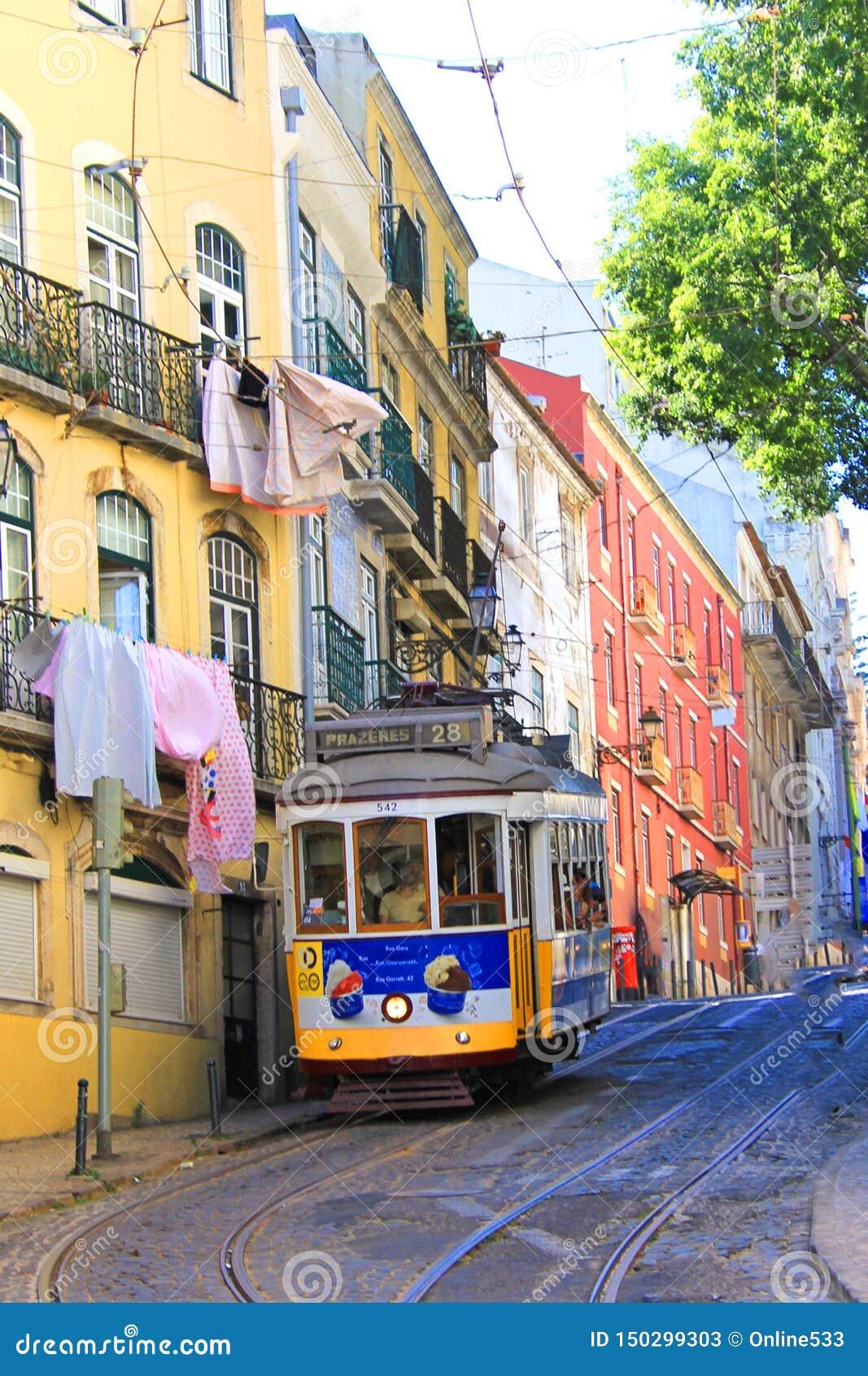 Желтый исторический трамвай в Лиссабоне управляя через старый городок alfama
