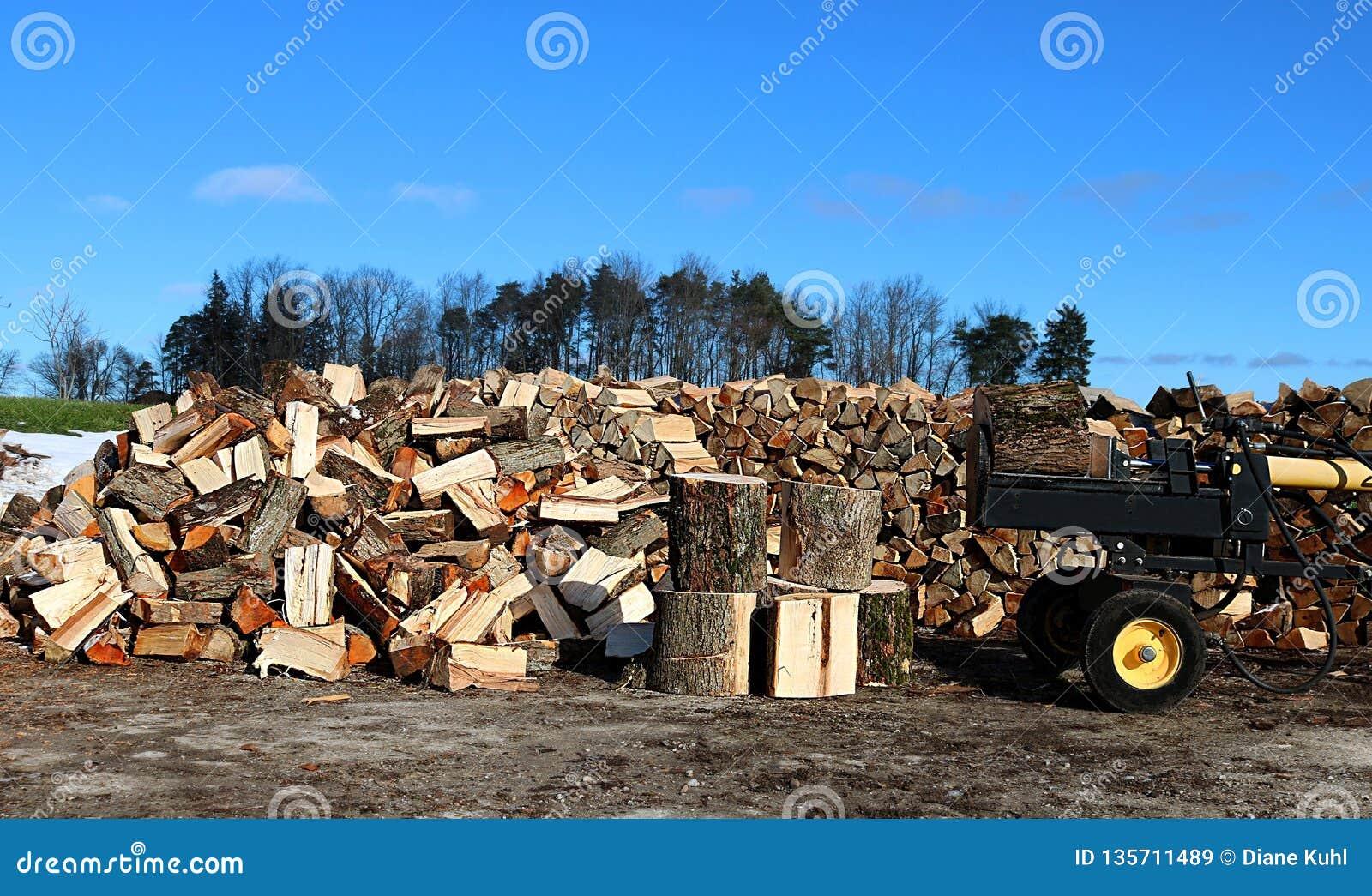 Желтый и черный деревянный splitter с блоками древесины, кучей разделенной древесины и деревянной кучей