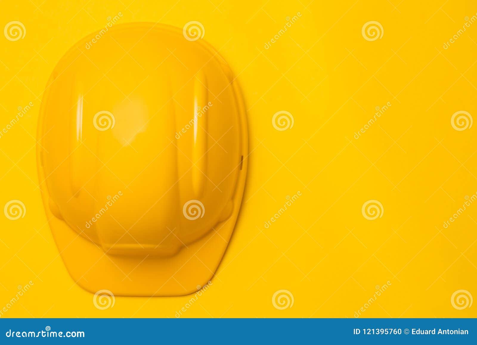 Желтый шлем на желтой предпосылке, головная защита конструкции, концепция, взгляд сверху