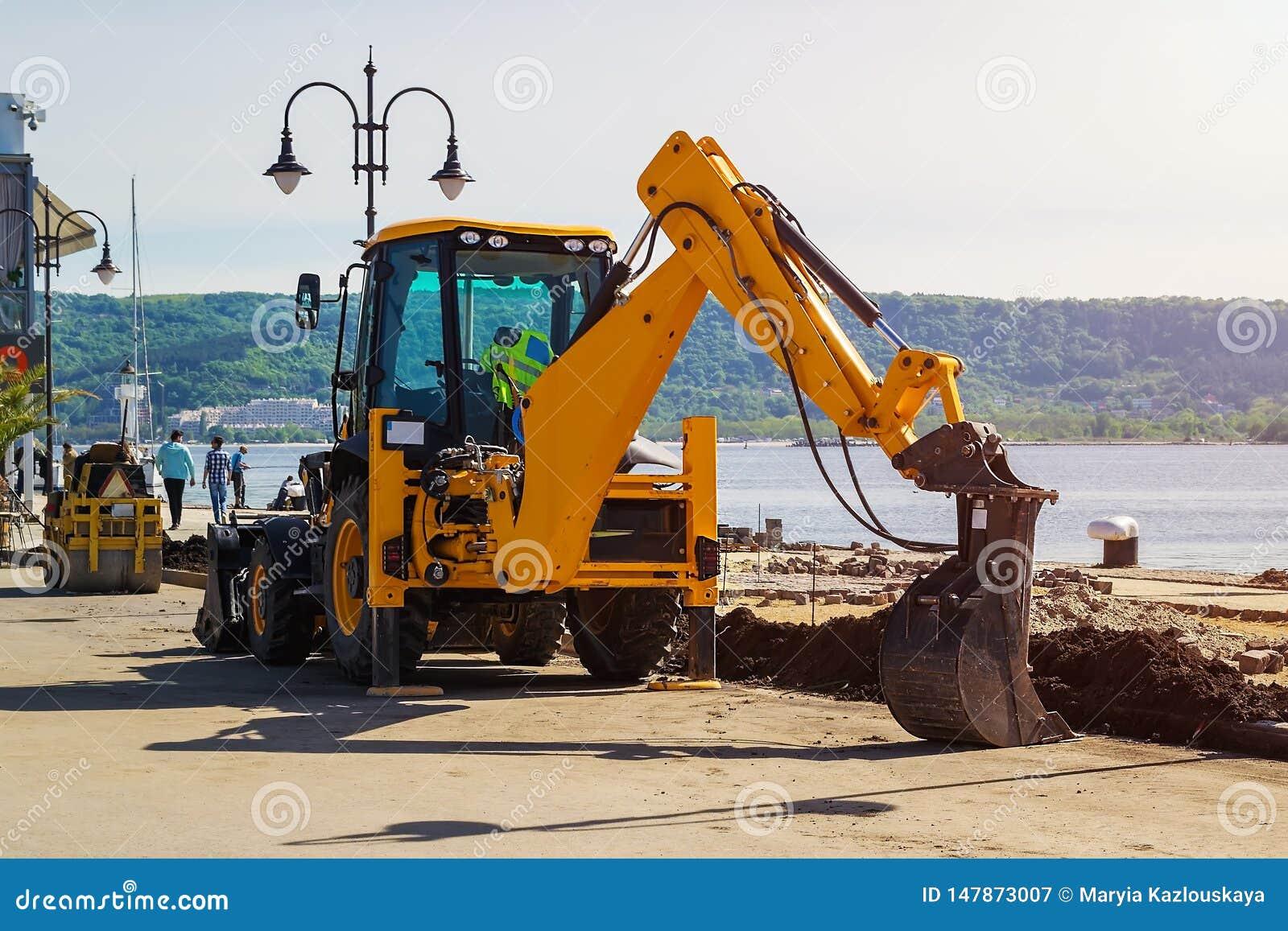 Желтый экскаватор с пониженным ведром стоит на месте работы строительства дорог в морском порте на солнечный летний день