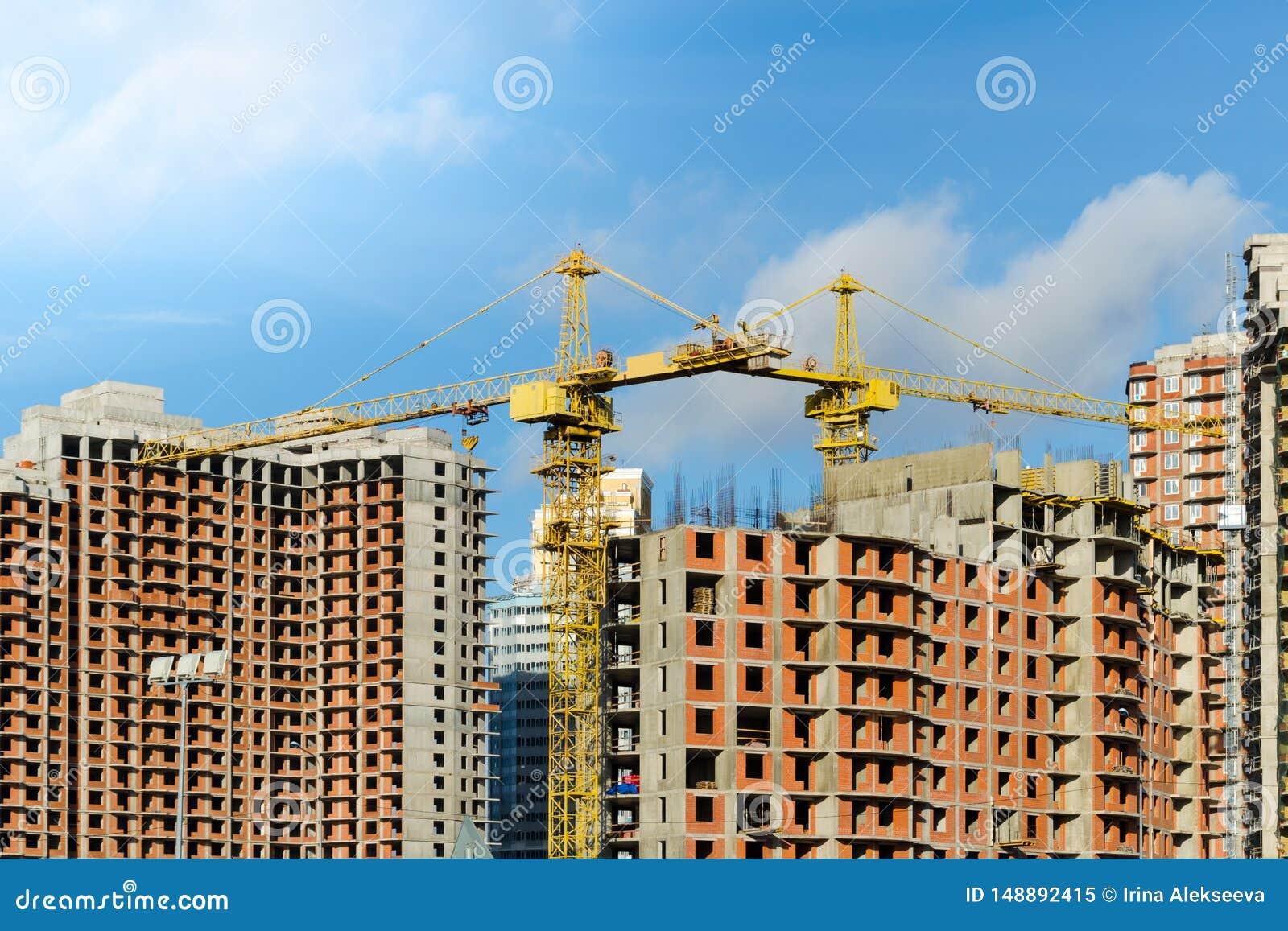 2 желтых крана конструкции на строительной площадке домов кирпича мульти-этажа против голубого неба