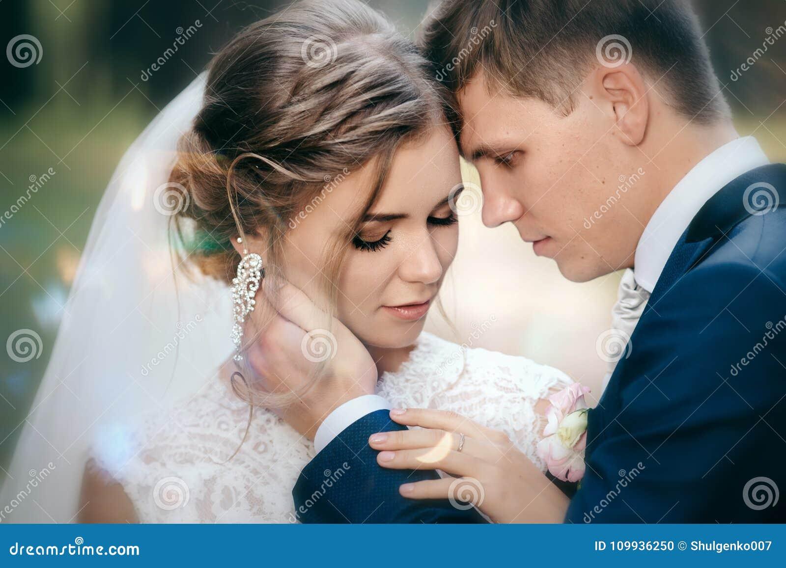 Жених и невеста в платьях свадьбы на естественной предпосылке Сногсшибательная молодая пара неимоверно счастлива венчание сбора в
