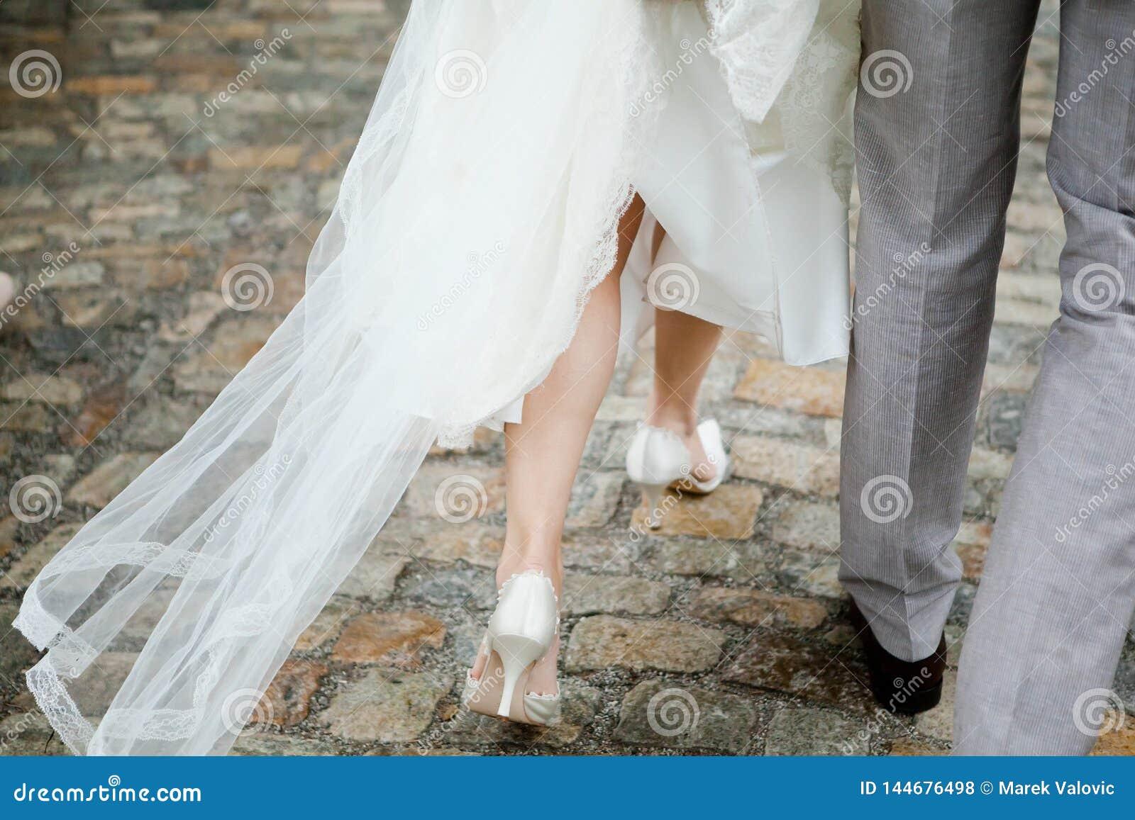 Жених и невеста идя, невеста деталей на ногах