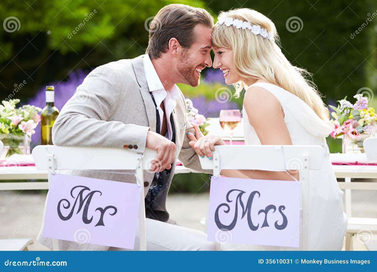 Жених и невеста наслаждаясь едой на приеме по случаю бракосочетания