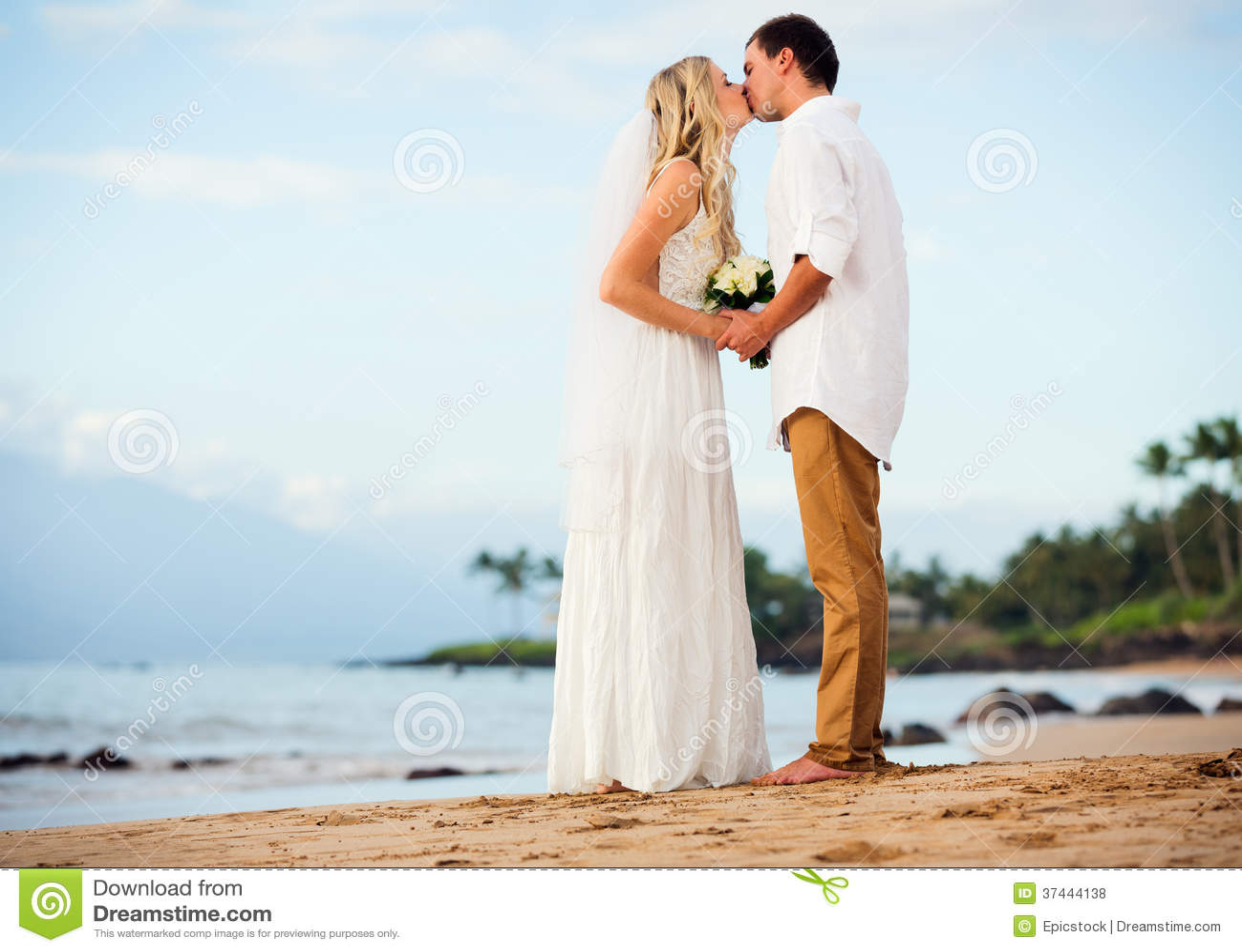 Жених и невеста на заходе солнца на тропическом пляже