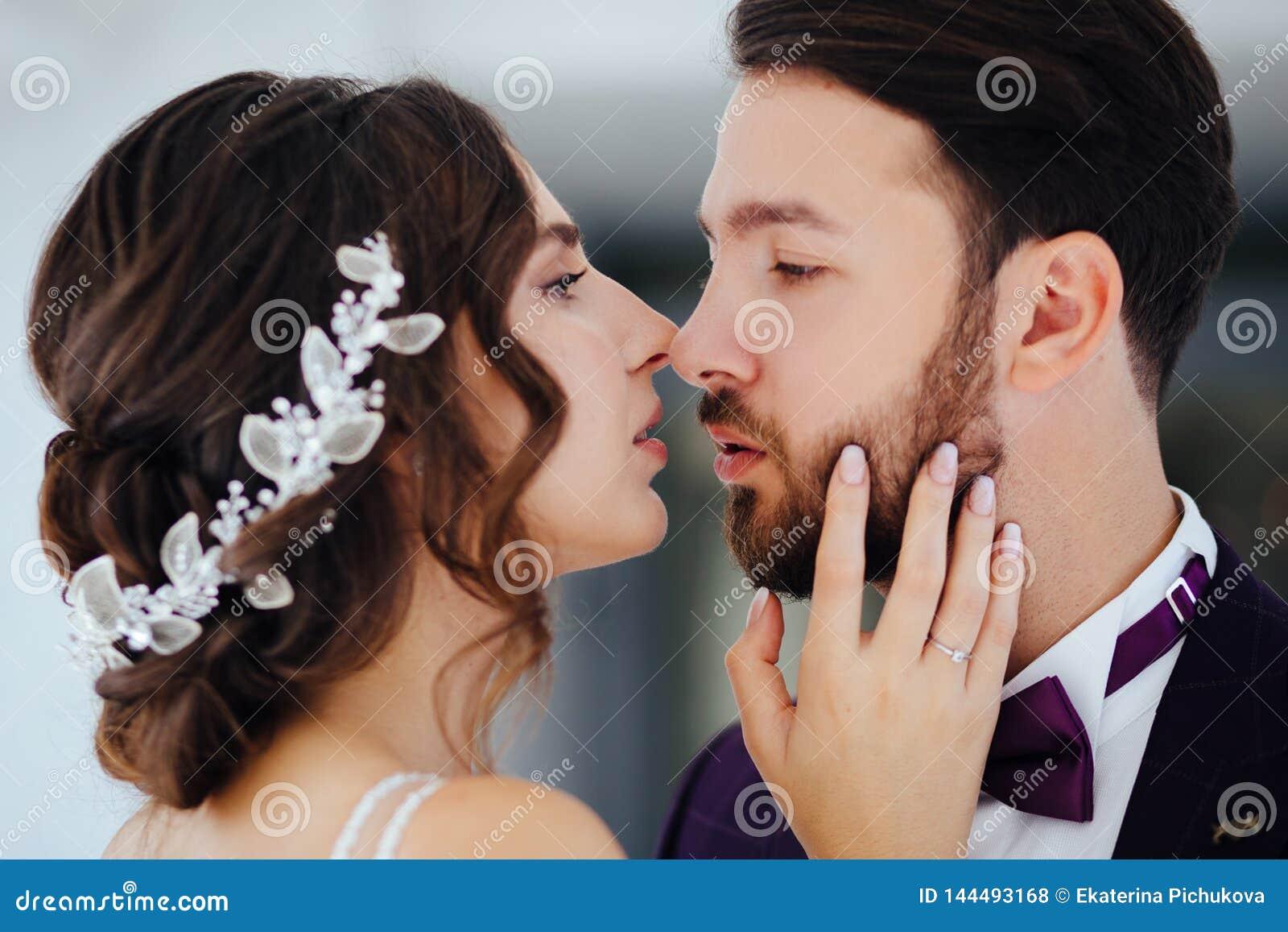 Жених и невеста обнимая и целуя Новобрачные