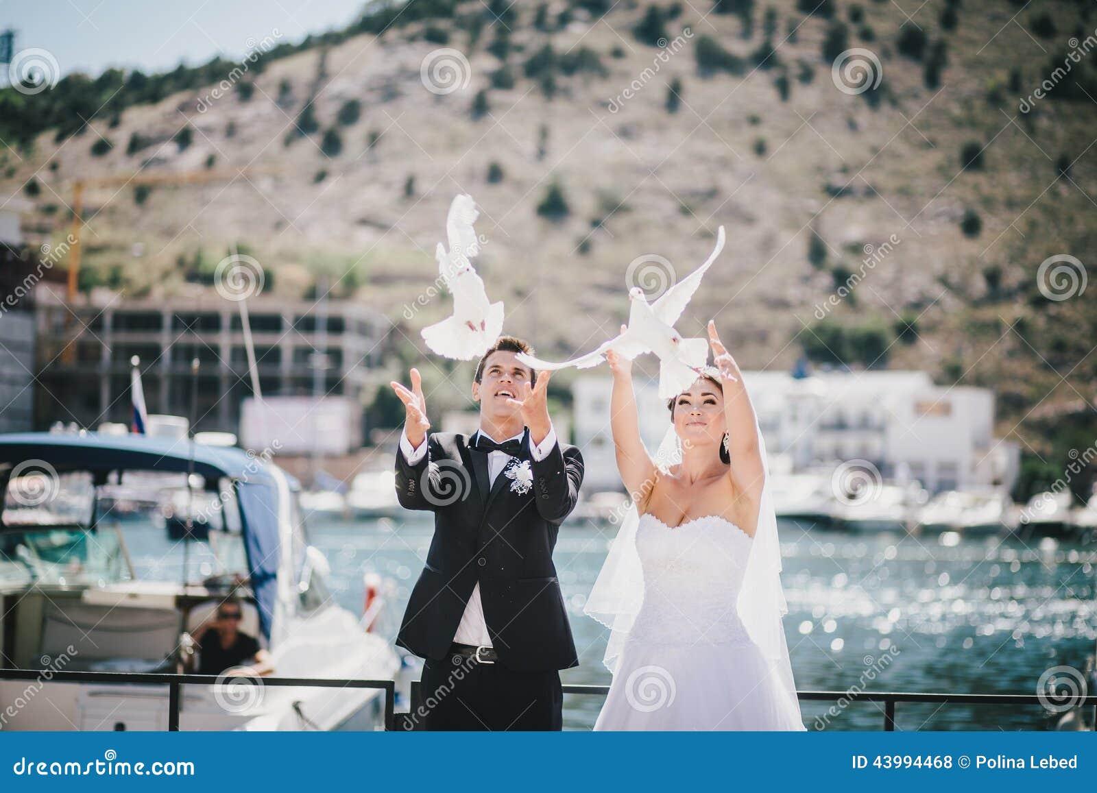 Жених и невеста представляя с белыми голубями свадьбы
