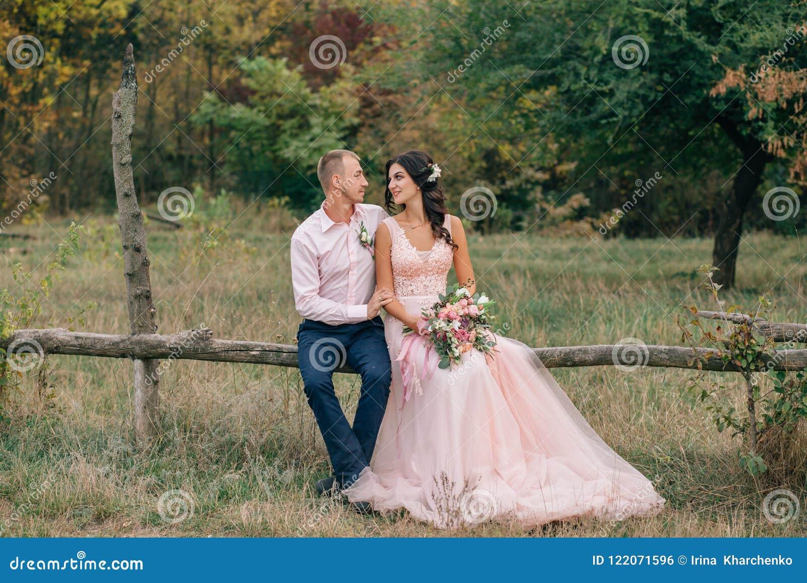 Жених и невеста сидит на деревянной загородке около ранчо Свадьба в осени стилизованна в розовых тонах _