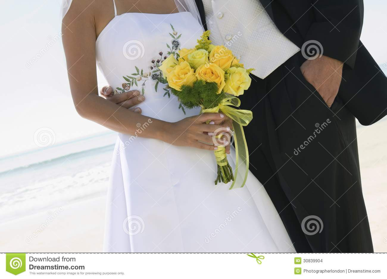 Жених и невеста с букетом на пляже (конец-вверх)