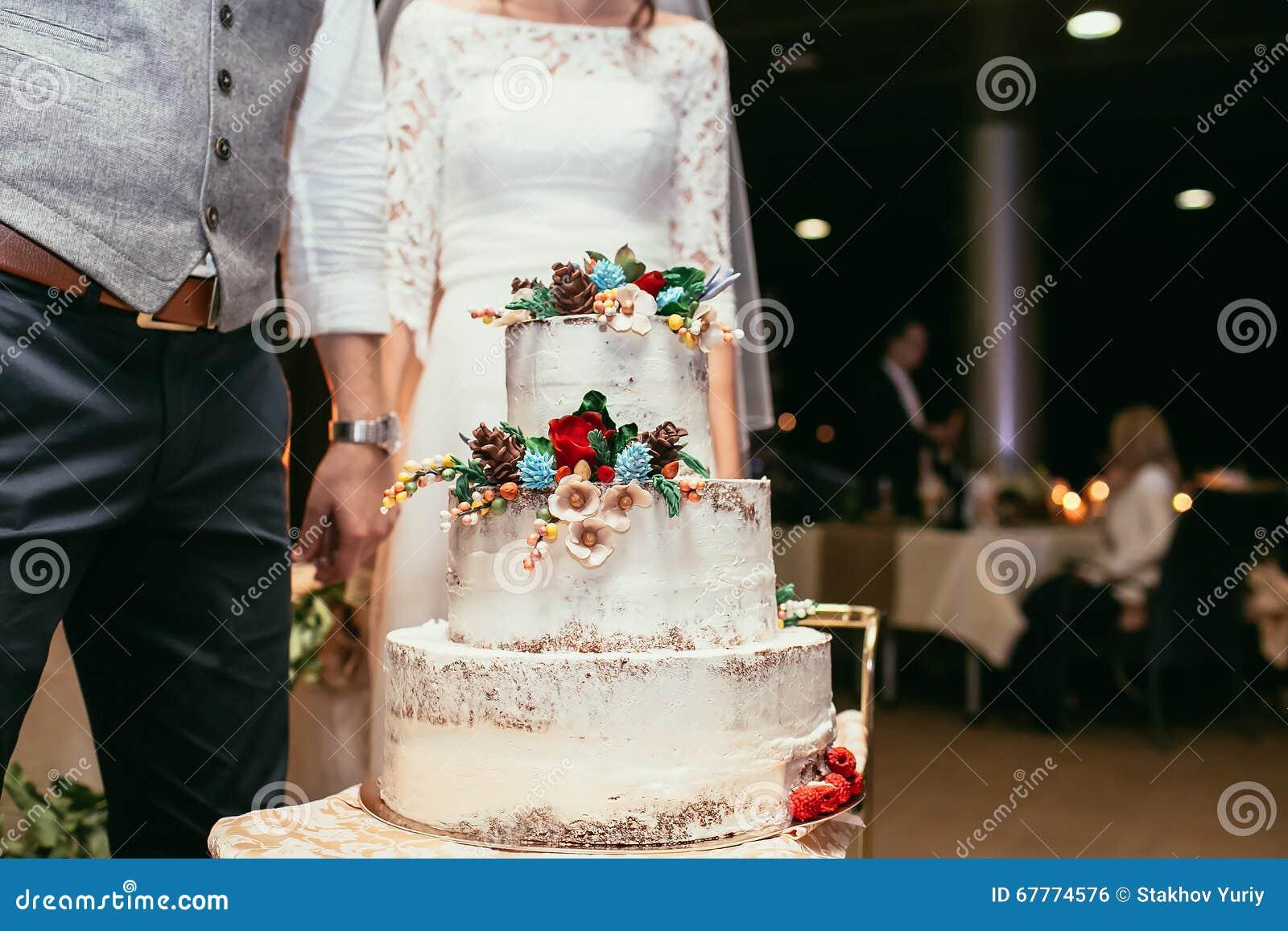 Жених и невеста с деревенским свадебным пирогом на банкете свадьбы с