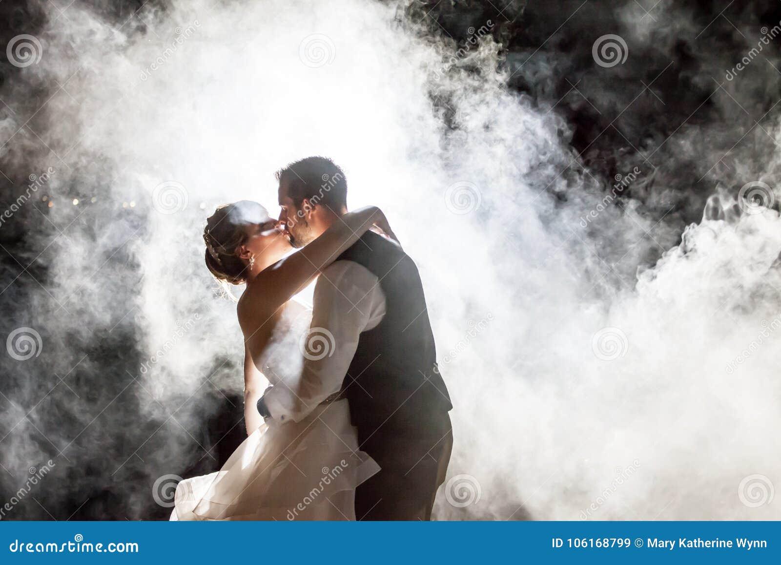 Жених и невеста целуя в тумане на ноче