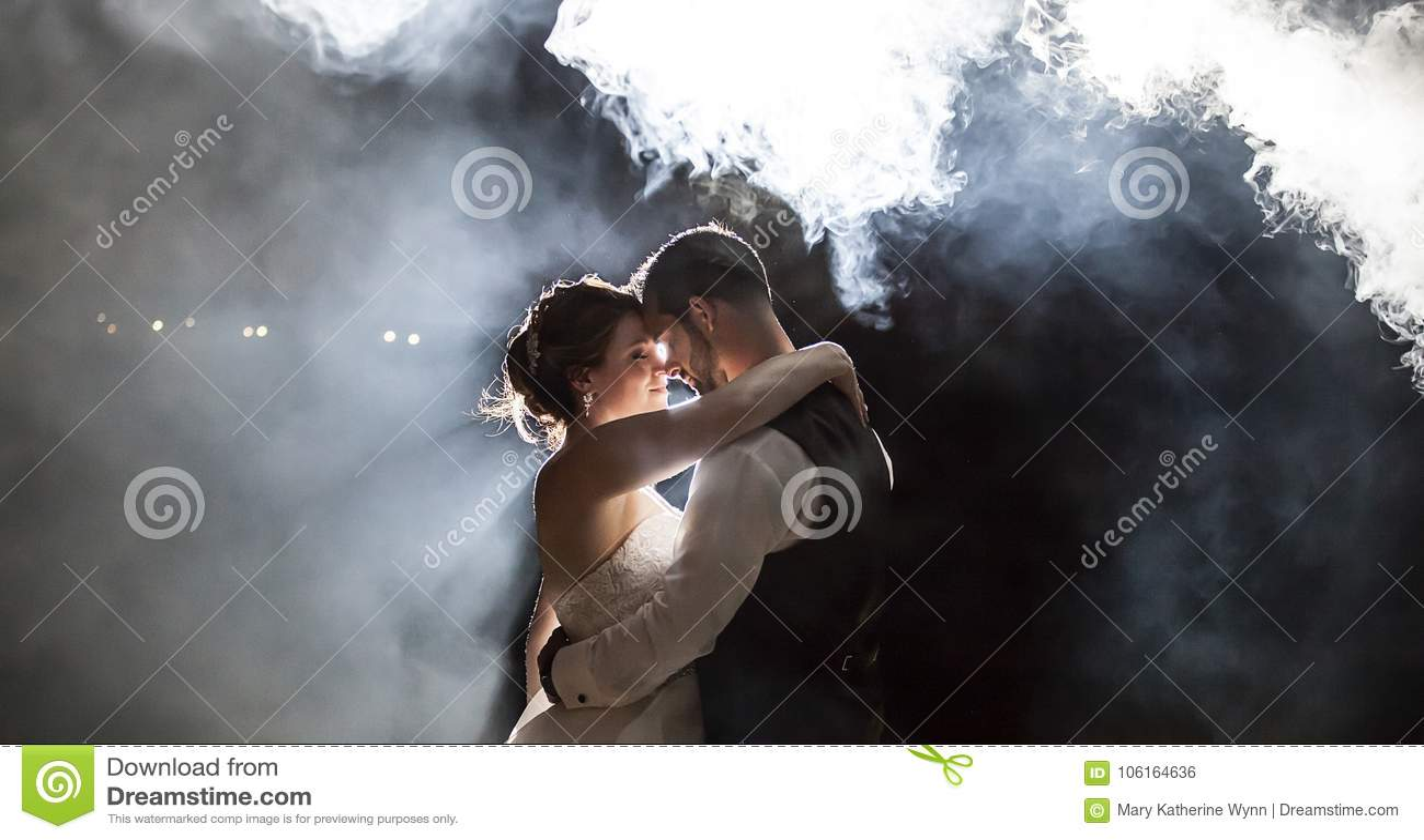 Жених и невеста целуя под туманом на ноче