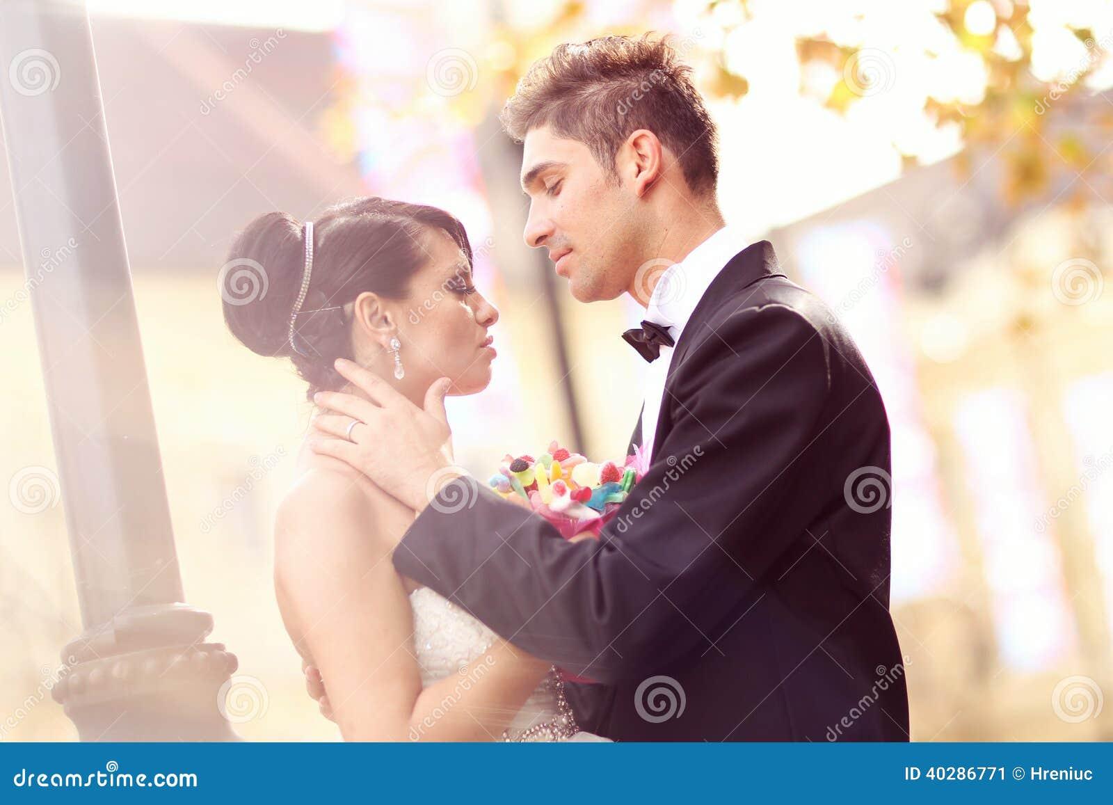 Жених и невеста целуя и обнимая в городе