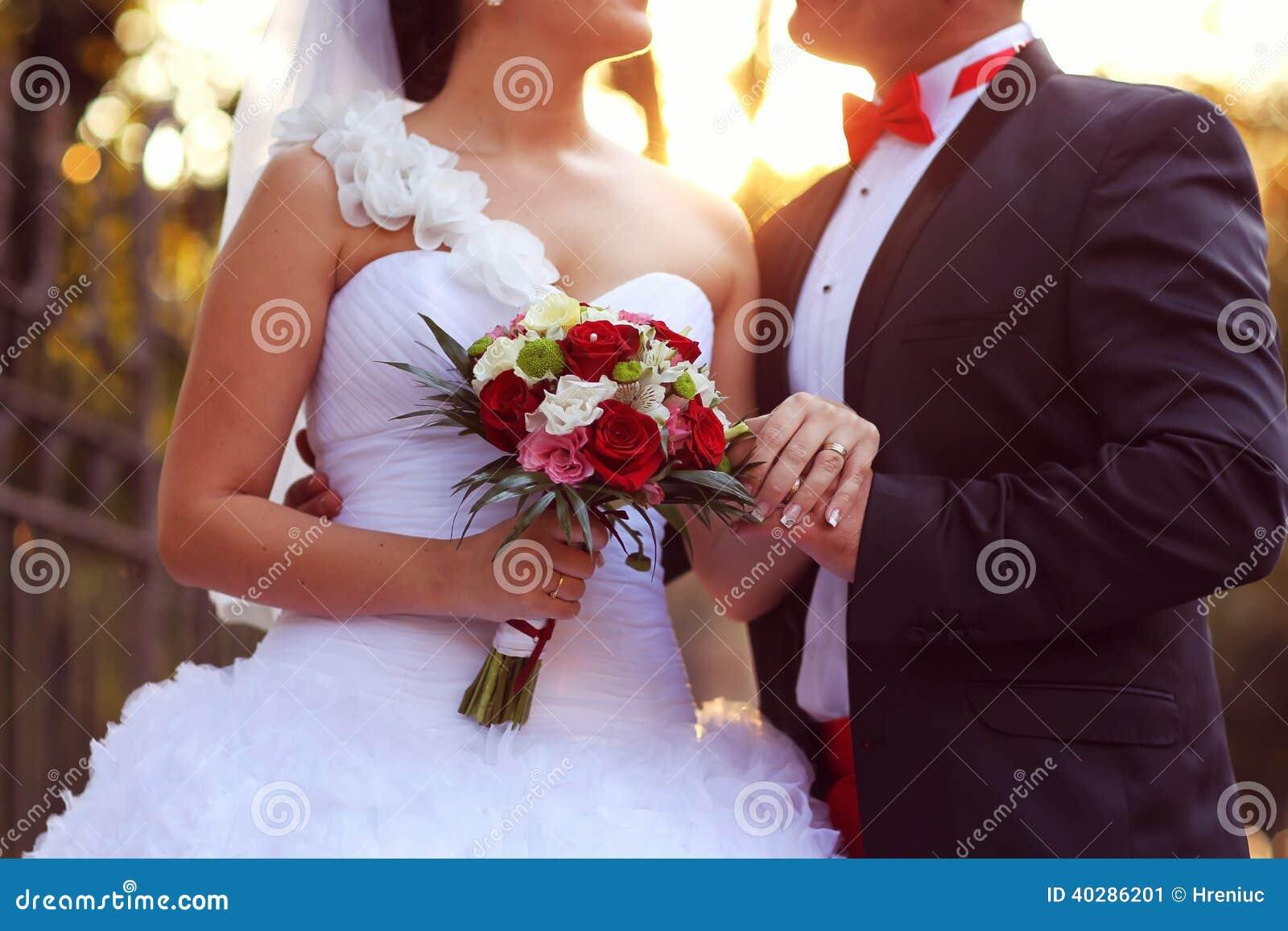 Жених и невеста целуя на заходе солнца с букетом цветка