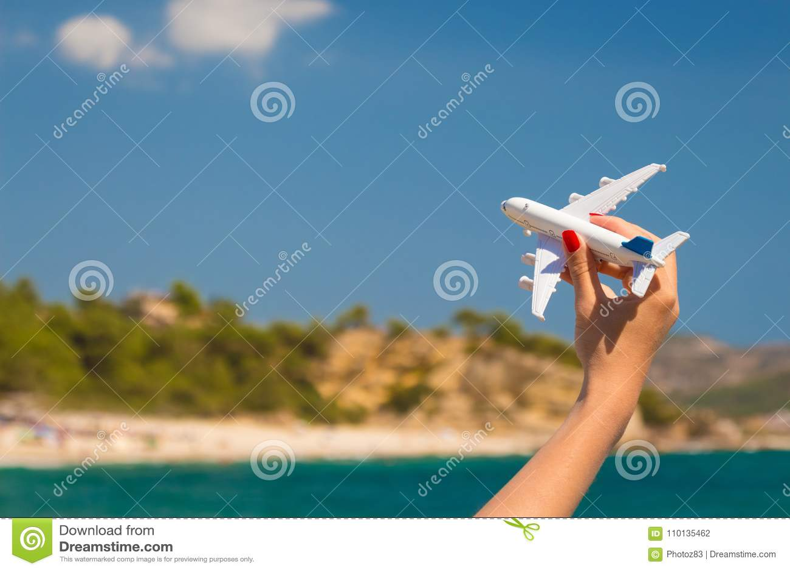 Женская рука держа игрушку самолета на пляже