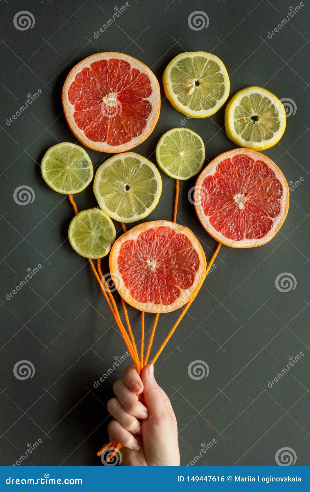 Женская рука держит воздушные шары с оранжевыми потоками сделанными кусков лимона цитруса, известки, апельсина, грейпфрута на чер