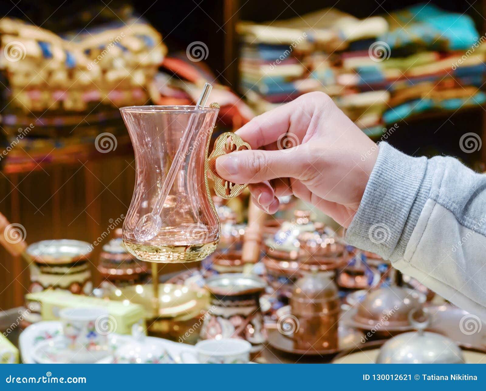 Женская рука держит стекло чая сувенира турецкое с ложкой